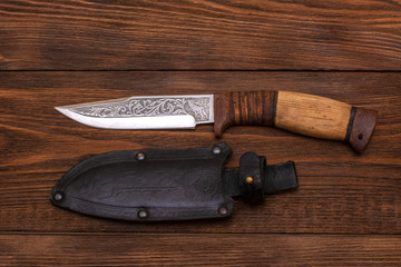hunting knife wth a wooden handle on dark wooden background. Steel arms weapon