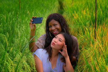 mixed ethnicity Asian Korean girl and black African American woman taking girlfriends selfie with mobile phone together isolated at rice field enjoying tropical holidays
