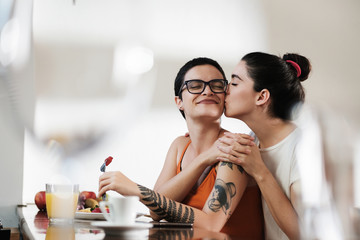 Young Lesbian Couple Kissing and Romantic During Breakfast