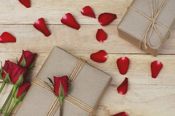 Eco friendly brown paper wrapped gift box present decorated with rose and other flowers on wooden background, valentine ornamental concept