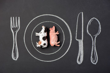 Toy pig and cow on a plate in the figure on a chalk board