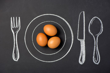 Boiled chicken eggs on a plate in the figure on a chalk board