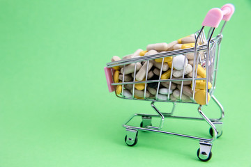 Small shopping cart full of pills on green background. Medicine and pharmacy concept