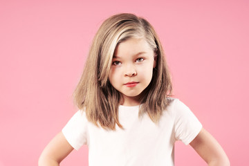 Portrait of a little serious blonde girl over pink background, close up