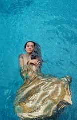 schöne junge stolze Frau in goldenem Kleid, Abendkleid schwebt schwerelos elegant schwimmend im Wasser im Pool dunkel braune Haare treiben in türkisem Wasser