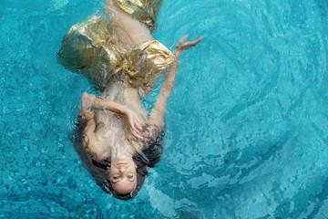 Draufsicht einer schönen jungen sexy Frau in goldenem Kleid, Abendkleid, Tuch schwebt schwerelos elegant schwimmend im Wasser im Pool