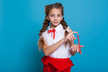 little girl with two braids with colored pencils