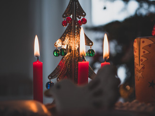 Christmas candles and Christmas bell. In background Christmas tree.
