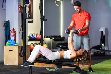 Personal trainer assisting client with weight training, lifting dumbells, lying on bench