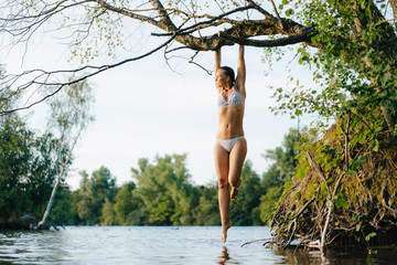 Woman wearing a bikini hanging on tree branch over a lake