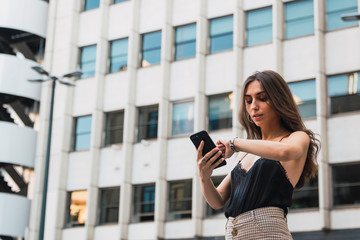Portrait of young woman with cell phone checking the time