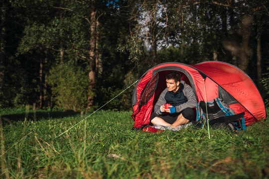 Man camping in Estonia, sitting in tent, drinking coffee