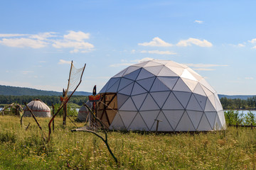 white geodesic dome on a sunny summer day in field