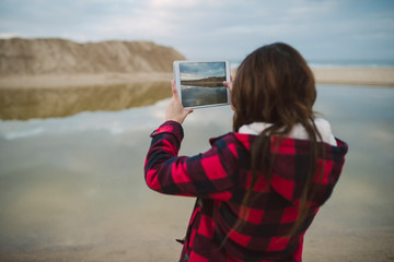 Young woman taking photo with tablet on the beach