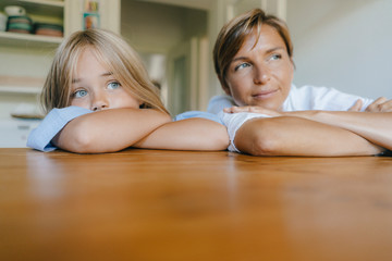 Mother and daughter leaning on kitchen table at home