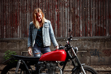 Smiling young woman standing next to motorcycle