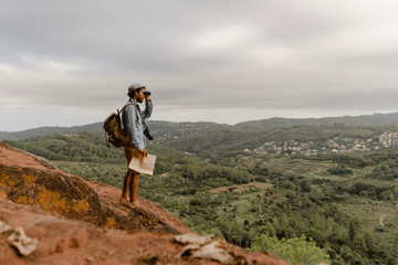 Young man with backpack, standing on a mountain, looking at view, using field glasses