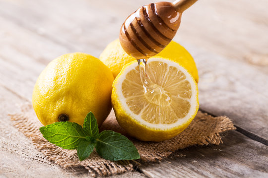 Closeup of lemon and honey on wooden table