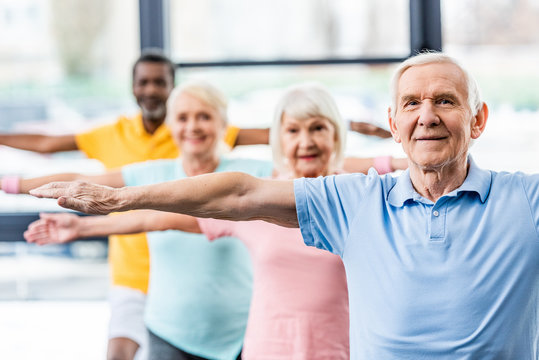 selective focus of multicultural senior athletes synchronous doing exercise at gym