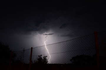 Urban lightning strike with fence in foreground