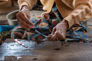 Mujer trabajando la flor de loto para hacer seda. Lago Inle, Myanmar