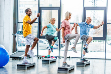 side view of multiethnic senior athletes synchronous exercising on step platforms at gym