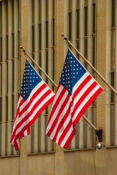 (2) Amaerican Flagshang outside a building in NYC.
