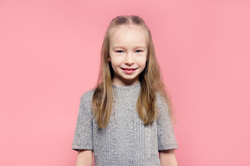 Portrait of a happy child girl over pink background.