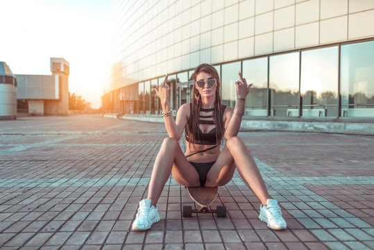 Beautiful girl sitting on a skateboard. The gesture of the hand shows middle finger. The concept of not trust, aggression. Long hair, black swimsuit. Confident look. Emotion leave me alone, go away.