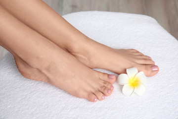 Poster Pedicure Woman with smooth feet on white towel, closeup. Spa treatment