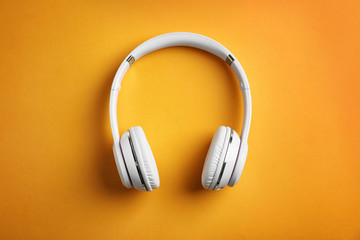 Wireless headphones on color background, top view