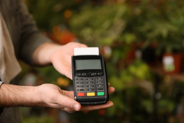 Man holding payment terminal in floral shop, closeup. Space for text