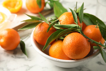 Bowl with ripe tangerines on table. Citrus fruit