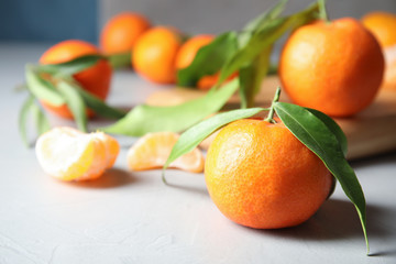 Ripe tangerine with leaves on table. Space for text