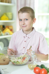 Cute boy making dinner on kitchen table at home