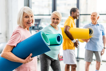 selective focus of senior sportswoman holding fitness mat and her friends standing behind at gym