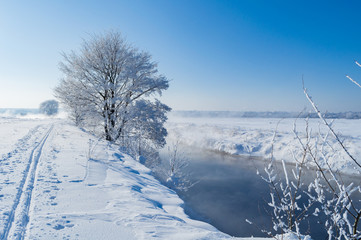 beautiful winter landscape riverside with trees in hoarfrost