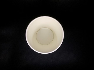 Top view of paper coffee cup on black background