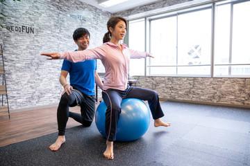 ジムでトレーナーとバランスボールをする女性
