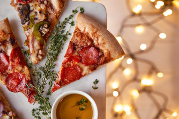 Christmas and New Year atmosphere. Hot Italian pizza with melting tomato, pepperoni and cheese on a white marbel cutting board. Background with lights in bokeh and selective focus.