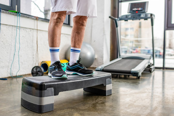 cropped image of senior male athlete standing on step platform at gym
