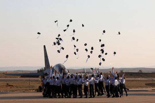 Israeli air force cadets toss their caps during a graduation ceremony for Israeli air force pilots at the Hatzerim air base in southern Israel