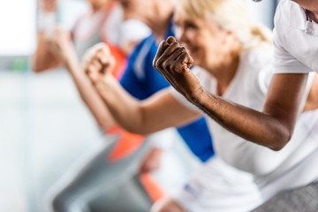 cropped shot of senior sportspeople synchronous exercising at sports hall