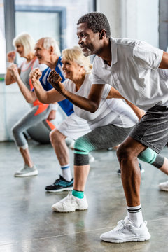 african american sportsman synchronous exercising with friends at sports hall