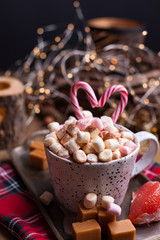 Cocoa with marshmallows in a white mug, different Christmas candies and sweets. Photo in dark style and free space for text. Candles and holiday decorations. Postcard and greetings.