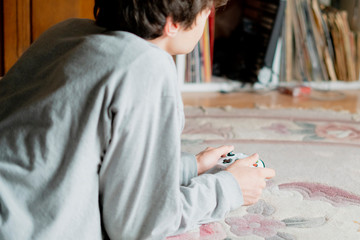 young boy lying on the floor carpet and playing video game at home f