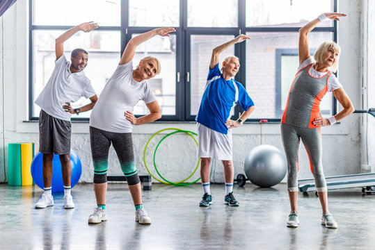 happy multiethnic senior sportspeople synchronous exercising at sports hall