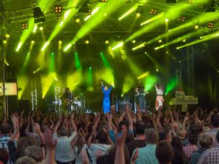 Blick über Publikum bei Retro-Konzert auf Bühne mit grüner Beleuchtung