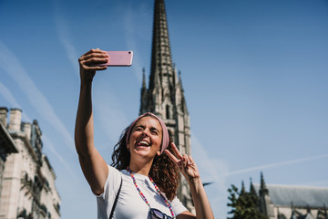 .Young woman doing sightseeing around the beautiful city of Bordeaux in France. Taking herself some pictures with her smartphone. Travel photography. Lifestyle.