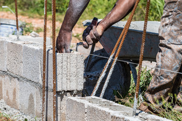 Hands of a black adult male mason/bricklayer laying cement block and using trowel to remove excess wet cement